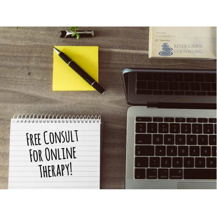 "Laptop and notepad on desk. Notepad says, ""Free Consult for Online Therapy!"""